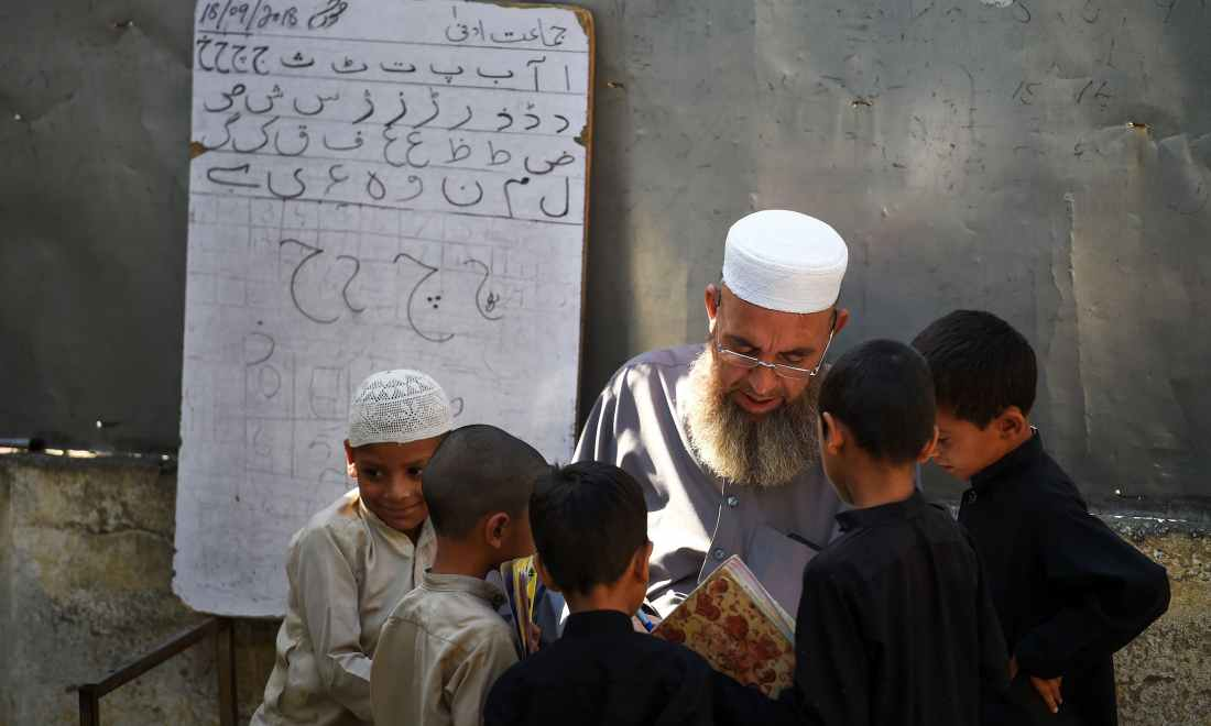 A teacher speaks with pupils attending a class at a school in Mingora. —AFP