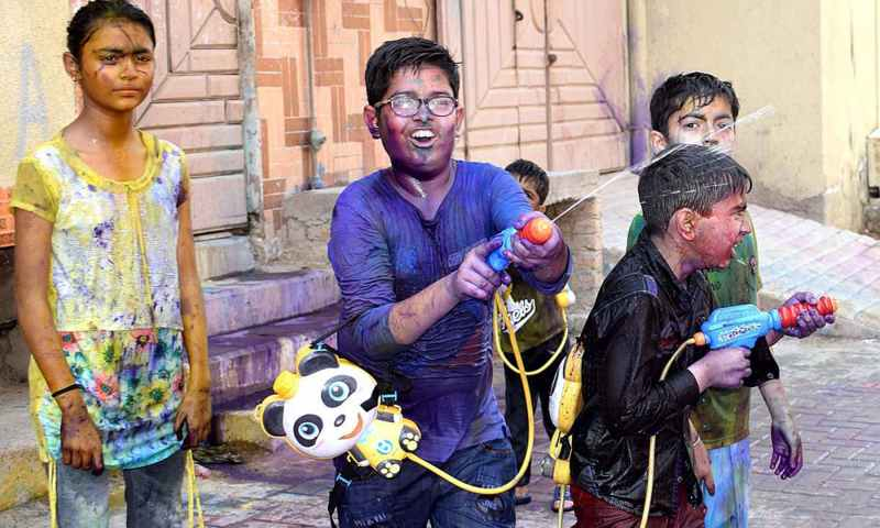 A group of children make use of water guns to shoot coloured water at one another as they celebrate Holi in Larkana, Pakistan, on March 20, 2019. — APP