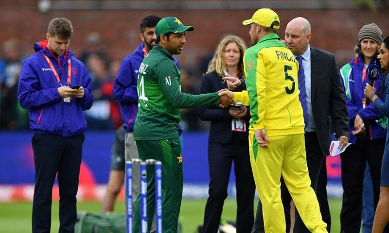 Skipper Sarfaraz Ahmed (C) shakes hands with Australia's captain Aaron Finch after winning the toss ahead of the match. — AFP