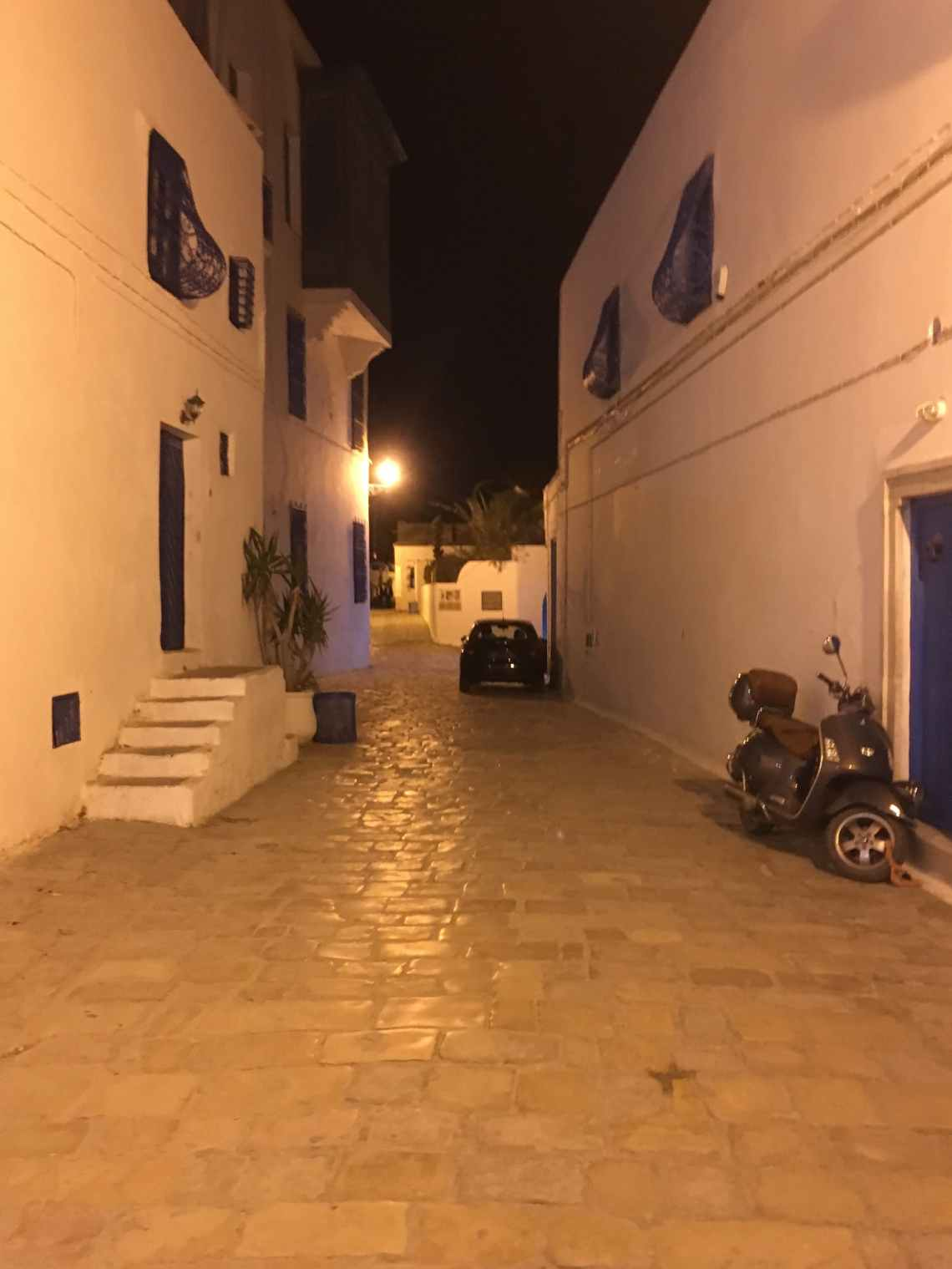 At nighttime, the streets in Sidi Bou Said are dimly lit with only a few people out and about.