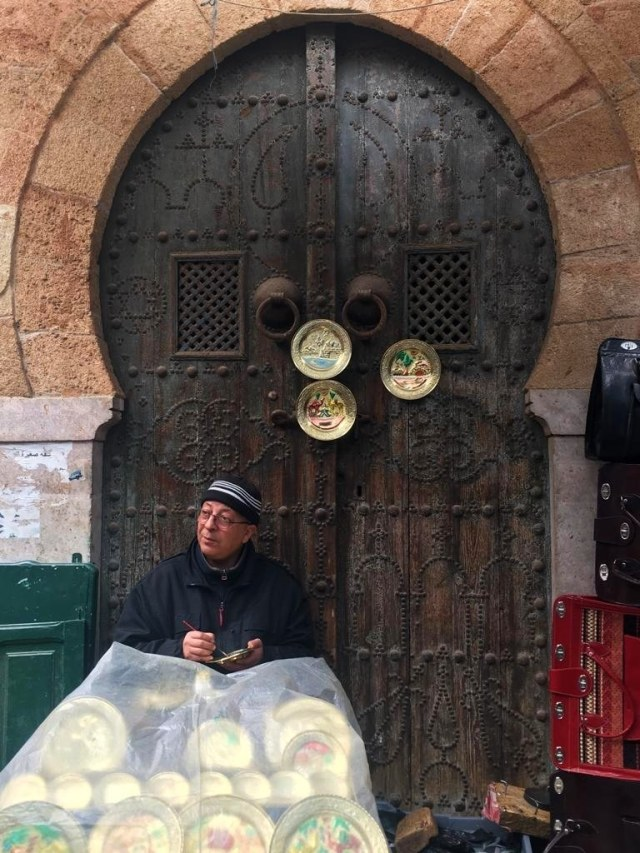A vendor paints small souvenir plates in the Medina.
