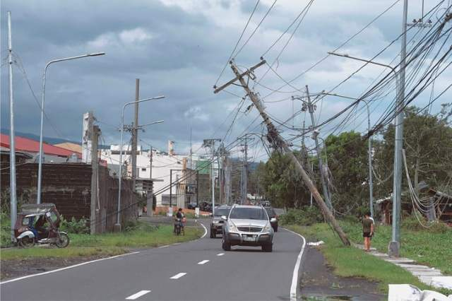 Manila: Vehicles pass by toppled electricity poles as the typhoon slammed Legazpi city on Tuesday.—AP
