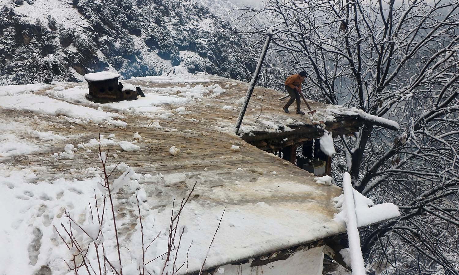 A boy clears a snow-covered roof of his family house after a heavy snowfall in Neelum Valley near the line of control. — Reuters