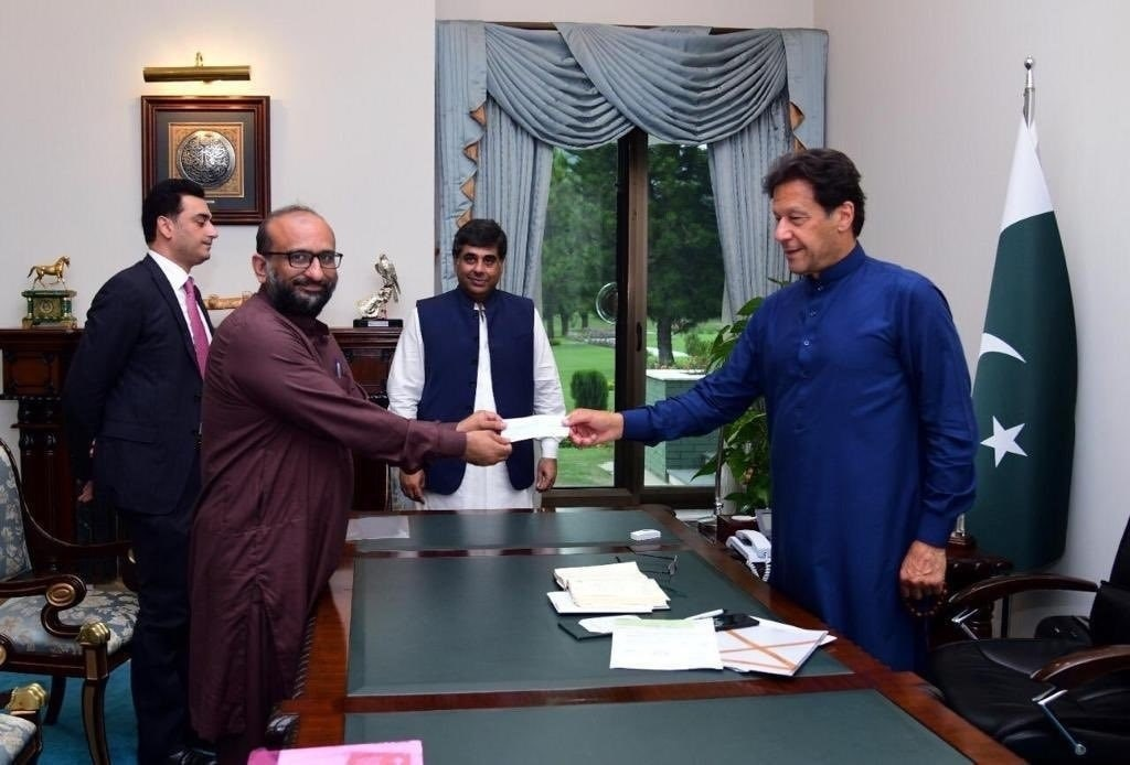 Faisal Edhi hands a cheque to Prime Minister Imran Khan, before testing positive for the coronavirus | PTI Twitter