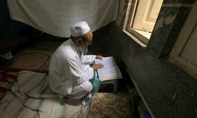 مسجد میں اعتکاف کرنے والے ایک بزرگ قرآن پاک کی تلاوت کر رہے ہیں— فوٹو: اے ایف پی