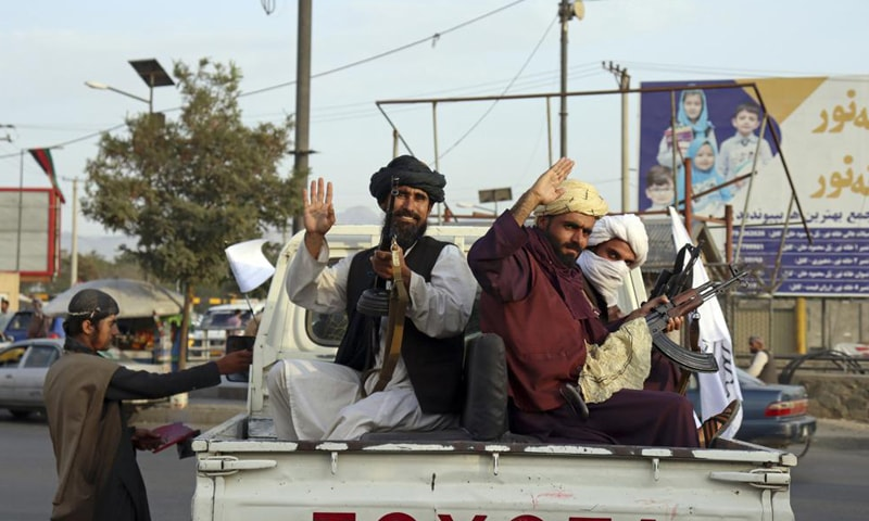 Taliban fighters wave from the back of a pickup truck, in Kabul, Afghanistan, Monday, Aug. 30, 2021. — AP