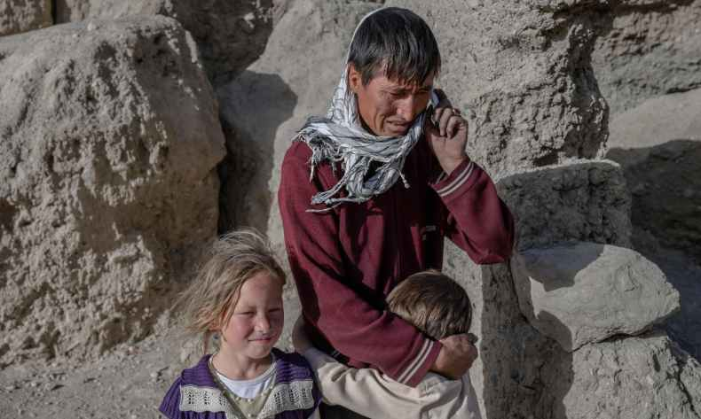 A Hazara man talking on his mobile phone as his kids stand next to him at their village where people live inside caves in Bamiyan, Afghanistan on October 3, 2021. — AFP