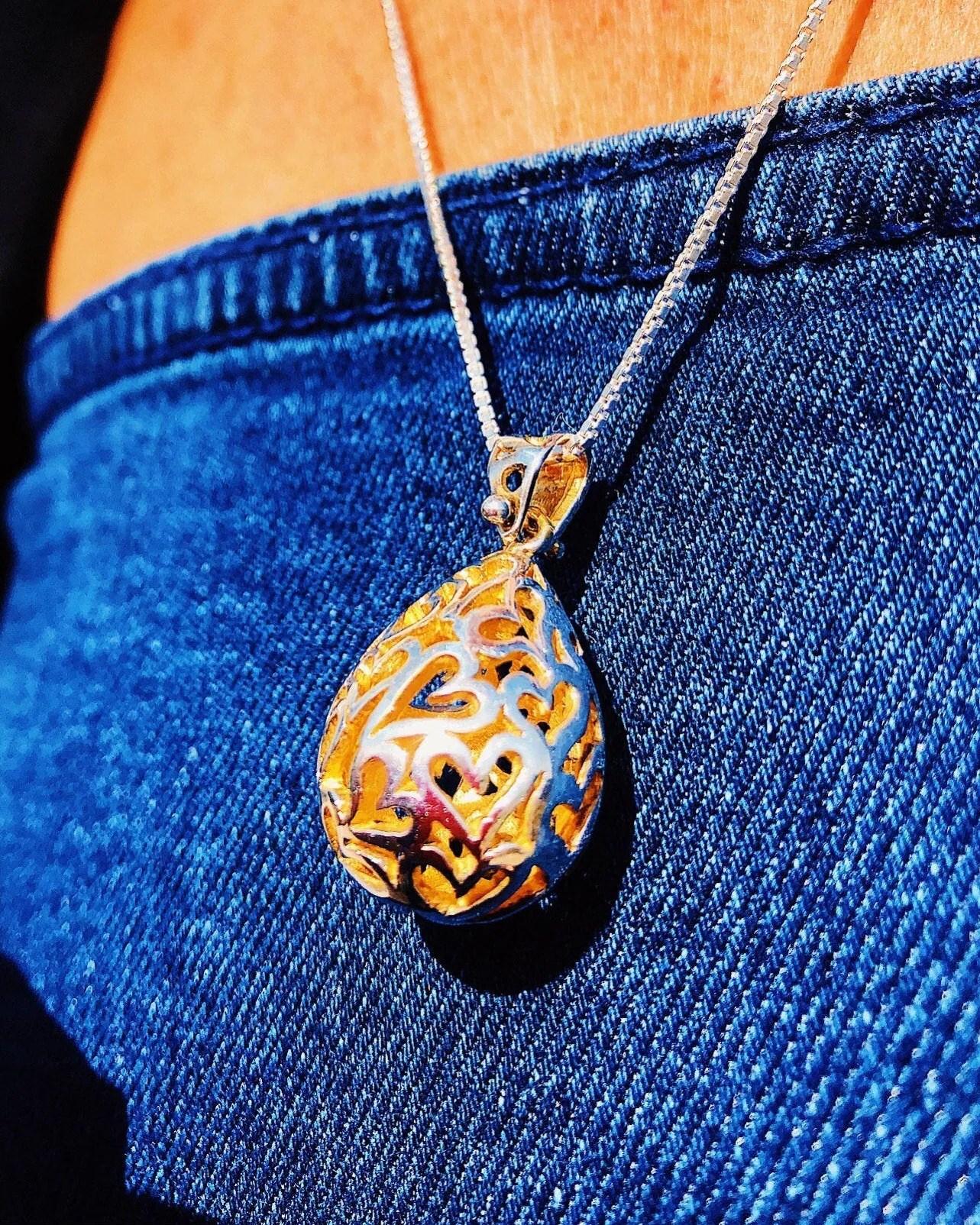pendentif pour les amoureux avec des coeurs coupés dans une goutte d'argent, l'intérieur de la goutte est plaqué or 14kt.