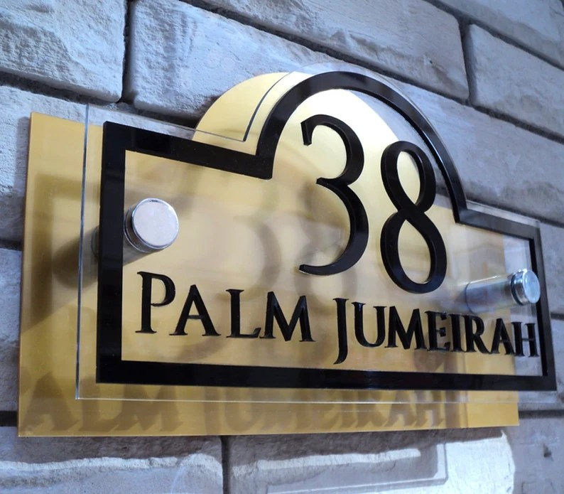 """Photo of an address sign mounted to a white brick wall. Sign is gold colored with black lettering and border. Sign says """"38 Palm Jumeirah""""."""