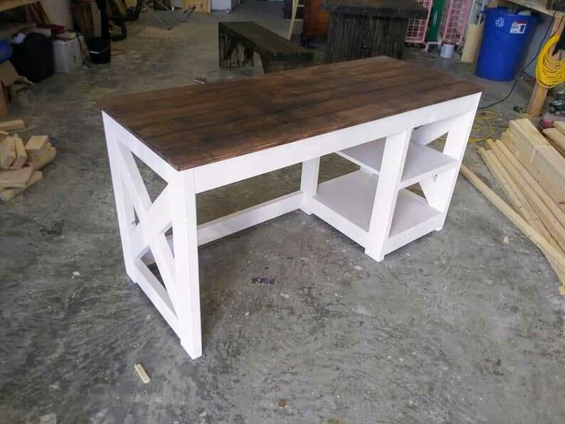 Photo of Farmhouse-style home office desk. Desk is white with dark brown wood top surface and is sitting in a wood workshop space.