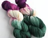 Indie dyed silver sparkle sock yarn, superwash merino/nylon/stellina sparkle sock/fingering yarn. Luna yarn, plum pink, green and speckles.