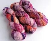 Hand dyed sparkle sock yarn, superwash merino/nylon/stellina sparkle sock/fingering yarn. Carole Did It, pinks purples oranges, variegated.