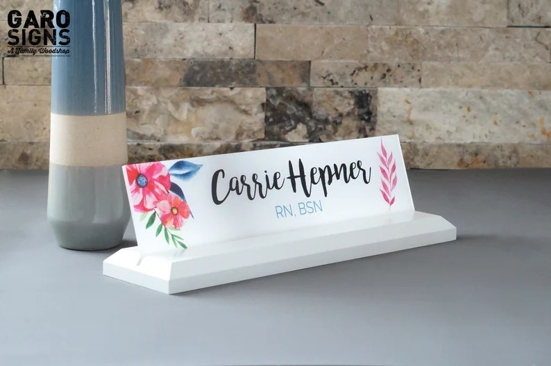 """Photo of a name placard sitting on a grey surface with a marble background and a colorful decor object behind it. Name placard has a white base and white and floral colors on the placard. Placard says """"Cassie Hepner RN BSN"""""""