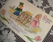 Antique Vintage Victorian Easter Greeting Embossed Postcard Early 1900s Dutch Boy Girl carrying gift box with Tulips Windmill Easter Chicks