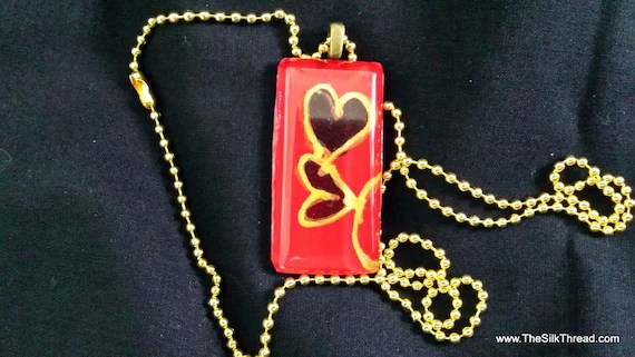 "Two gold hearts hand painted on red silk by artist. Beautiful 1"" x 2"" pendent necklace with 24"" chain, free organza gift bag"