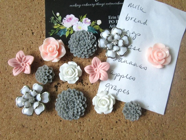 Photo of flower-shaped pins pinned into a cork board along with a handwritten grocery list and a printed invitation that is black with floral designs.