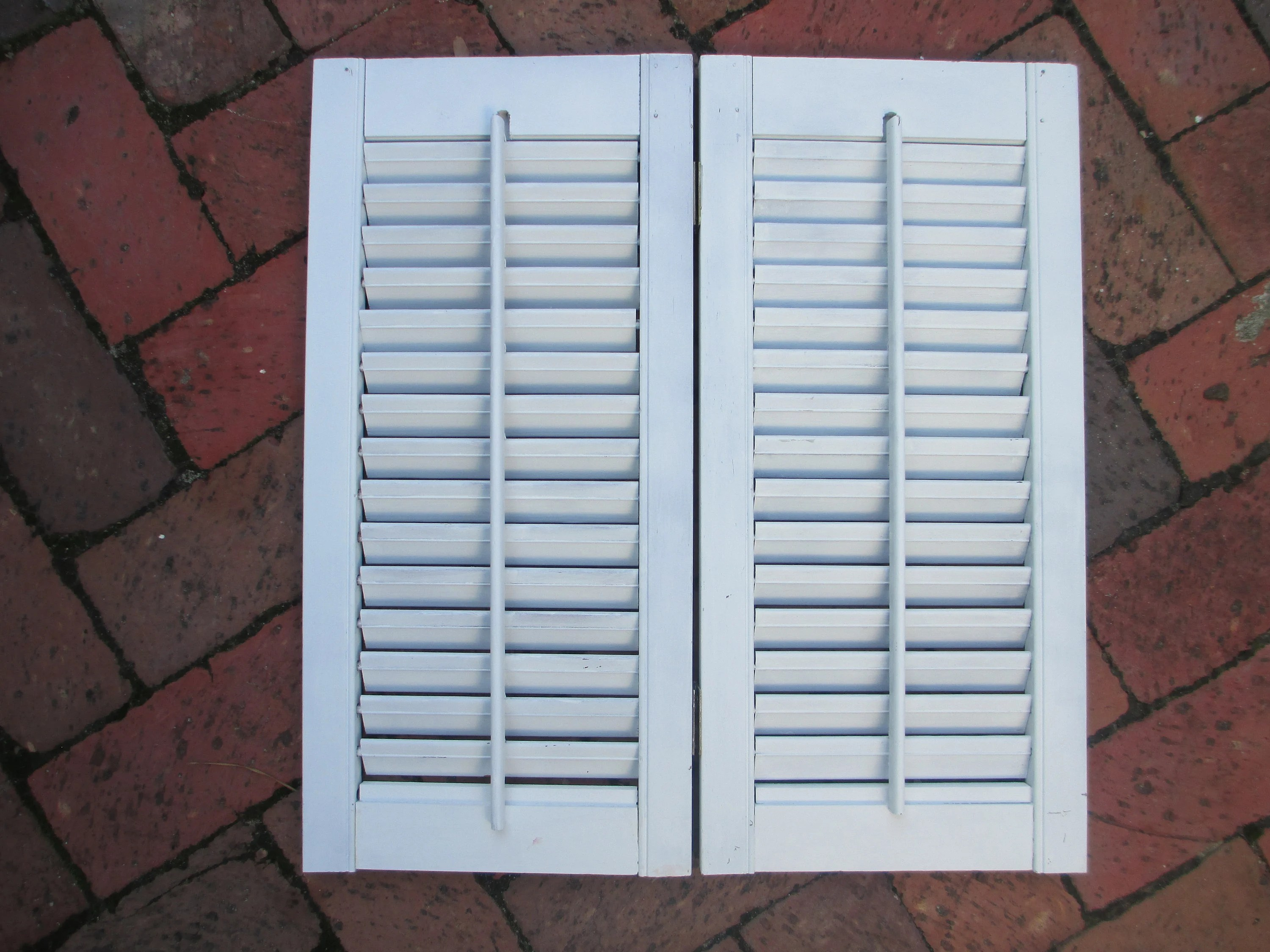 Two 19 Hinged White Shabby Wooden Louvered Interior Window Shutters That Open And Close With A Center Stick