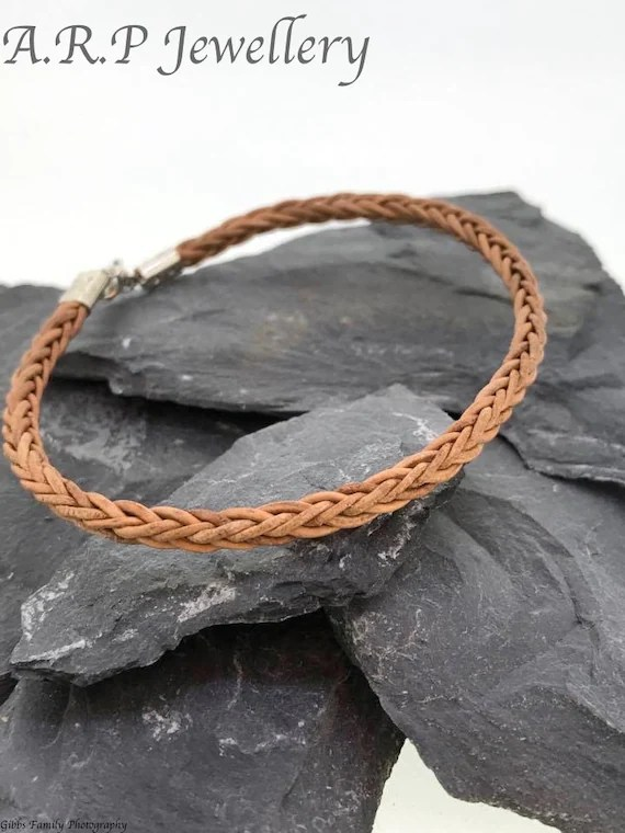 Leather bracelet in a plaited style in a light brown and tan colour