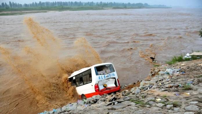 Un bus abandonné, rempli de sacs de sable est utilisé pour construire une digue de fortune dans cette zone inondée de Xingtai.