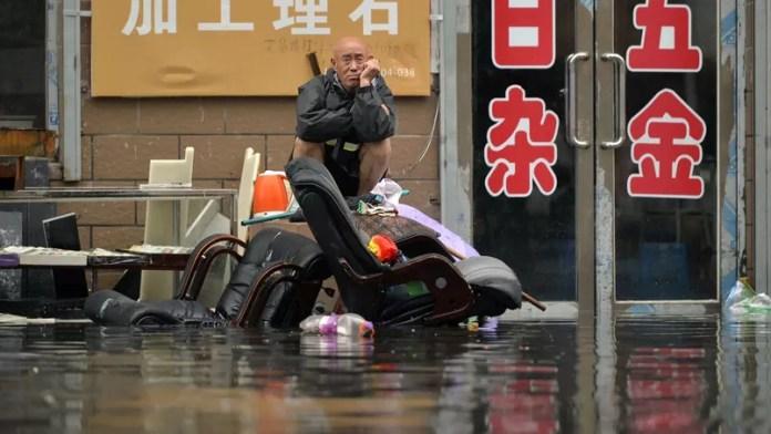 Les inondations ont détruit près de 50.000 maisons et 8,6 millions de personnes se retrouvent affectées par ces intempéries. Comme cet homme assis devant sa boutique inondée à Shenyang.
