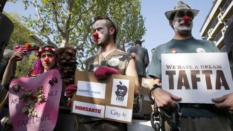 Des militants dénoncent les accords transatlantiques en cours de négociation entre la Commission européenne et les États-Unis à Paris en avril 2014. Crédits photo: PATRICK KOVARIK/AFP