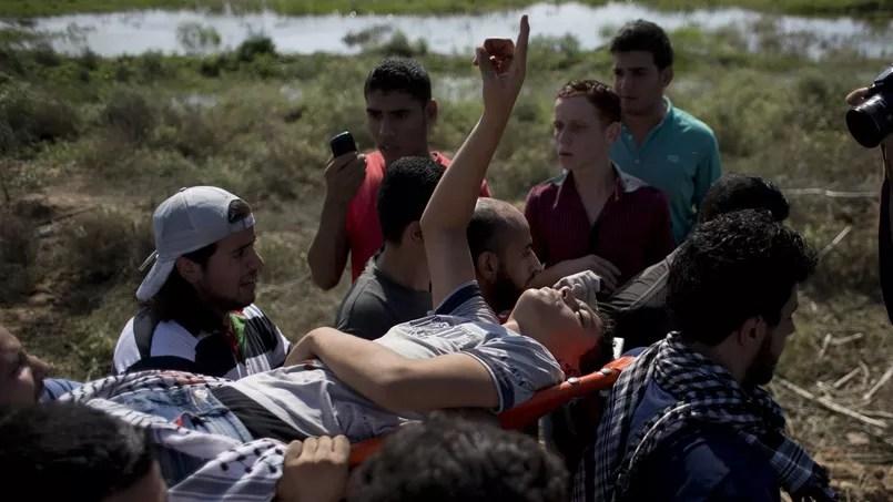 De jeunes Palestiniens transportent un camarade blessé par les tirs de soldats, vendredi, à Gaza, près de la clôture de sécurité les séparant du territoire israélien.