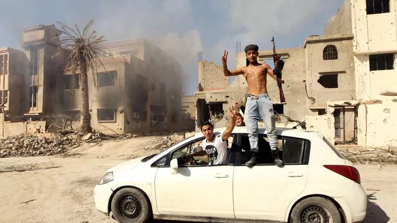 Des combattants fidèles au gouvernement libyen célèbrent, mardi, le retrait des troupes de l'EI du grand district d'al-Laithi, au sud-est de Benghazi.