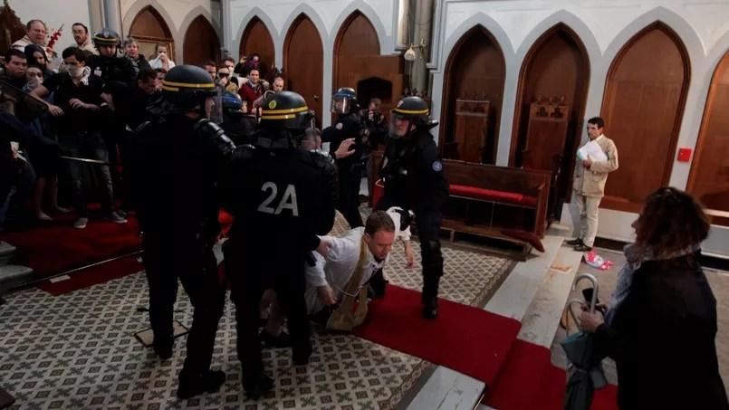 Un prêtre à terre pour resister à l'évacuation de l'église Sainte-Rita.
