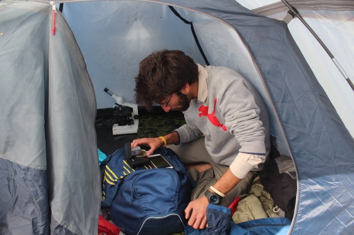 Munib Caption Here I am seen using the Iolight in a tent In the background is an abandoned standard compound microscope which due to its size and lack of clarity is rather field unfriendly iolight