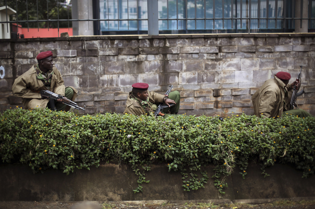 Kenya security forces are seen behind a wall outside the Westgate Mall in Nairobi, Kenya Monday morning, Sept. 23, 2013. Kenya's military launched a major operation at the upscale Nairobi mall and said it had rescued