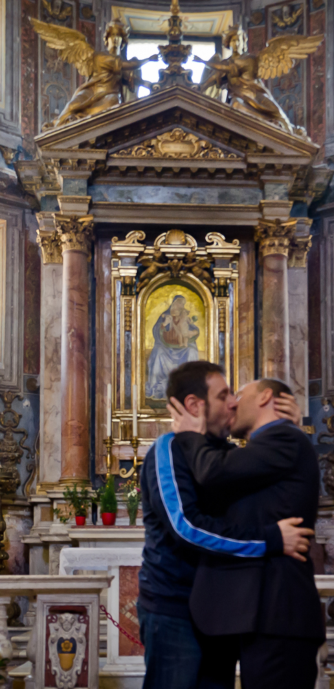 two men kiss in front of church altar