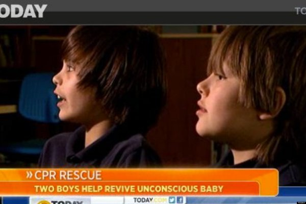 Two Boys Teach Woman Cpr ' Posters In School Cafeteria