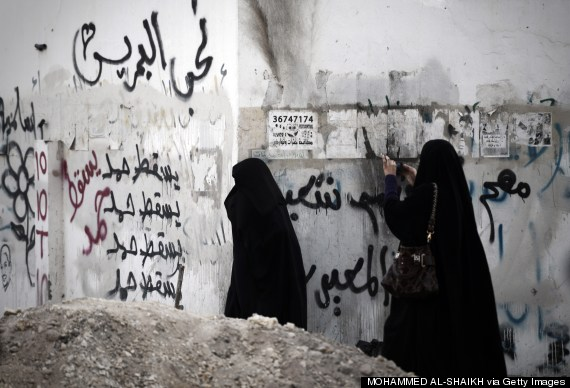 Bahrain protests. A Bahraini women use her mobile phone to take a picture during clashes with riot police