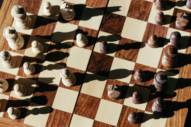 Wooden-white-and-brown-chess-pieces-cast-long-shadows-in-bright-sunlight-on-the-classic-chessboard-T
