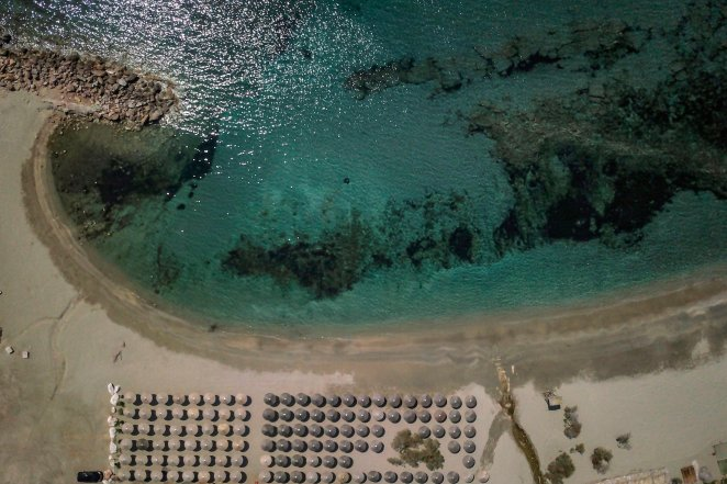 TOPSHOT - An aerial view taken on April 11, 2020 shows a beach of the costal zone of Athens, as the country remains under lockdown to stop the spread of COVID-19 disease caused by the novel coronavirus. (Photo by Aris Messinis / AFP) (Photo by ARIS MESSINIS/AFP via Getty Images)