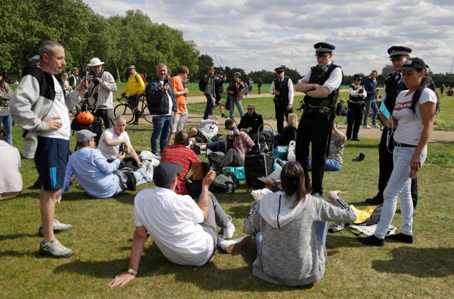 Police speak to people to break up a gathering during a mass gathering protest organised by the group called 'UK Freedom Movement', in Hyde Park in London as the country is in lockdown to help stop the spread of coronavirus, Saturday, May 16, 2020. The group claims that the coronavirus lockdown is illegal. (AP Photo/Kirsty Wigglesworth)