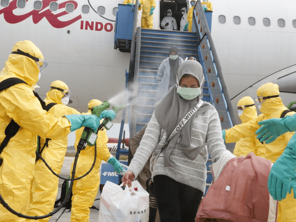 Officials spray passengers from Wuhan as they arrive in Indonesia ...