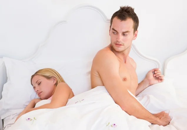 Man next to a sleeping woman with a surprised expression on his face