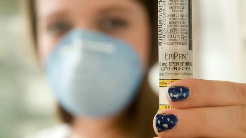 A high school student with severe nut allergies displays an EpiPen and wears a protective mask during an interview in Charleston, West Virginia in 2008.