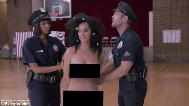Long arm of the law: As Katy stands defiantly, a pair of police officers quickly intervene