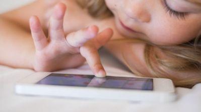 Ein kleines Mädchen spielt auf dem Smartphone.