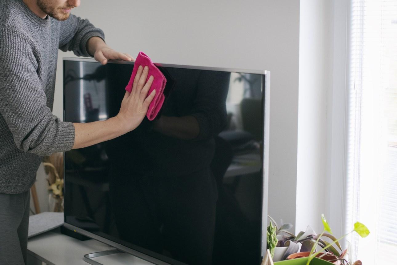 Крупным планом человек, чистящий экран телевизора - stock photo