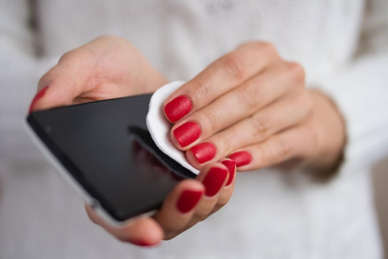 женщина чистит телефон