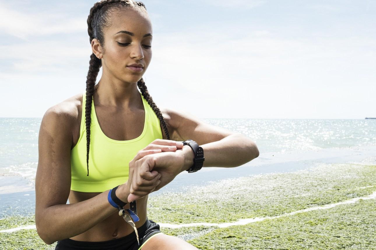 женщина смотрит на фитнес-трекер на ее запястье