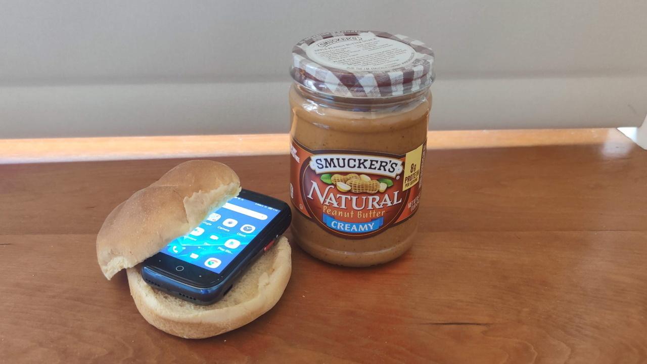 Телефон Jelly 2 на булочке рядом с банкой с арахисовым маслом.