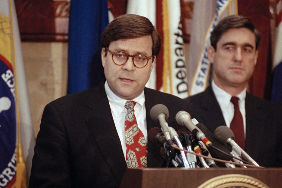 Then-Attorney General William Barr addressing reporters in Washington in 1991, as then Assistant Attorney General Robert Mueller stands nearby.