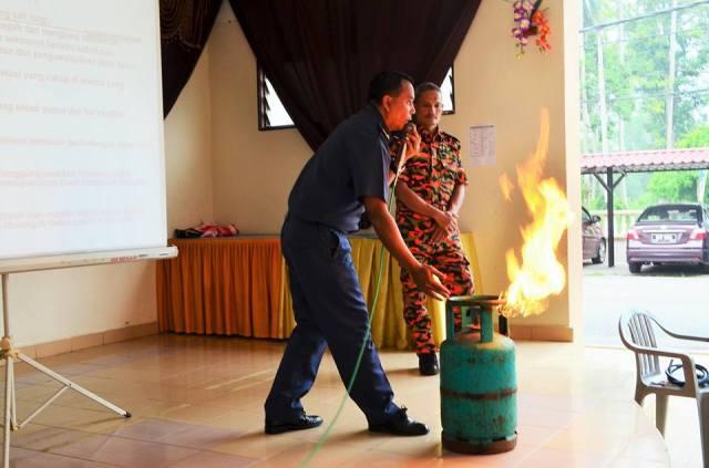 seorang anggota bomba memadamkan api dari tong gas