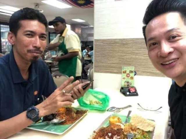 dua lelaki sedang makan di restoran