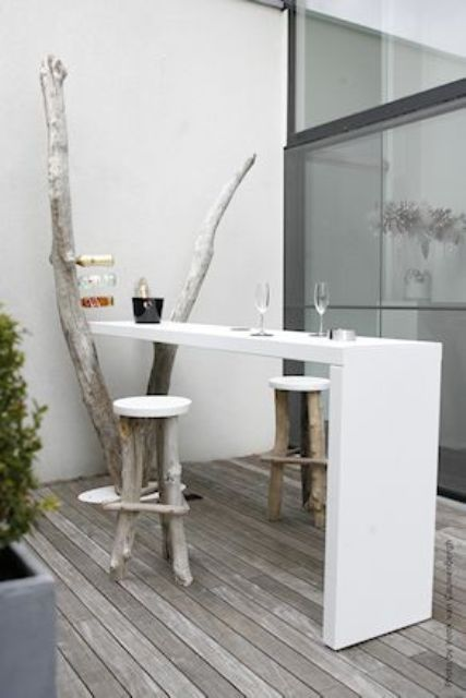 a white built-in tabletop and wood and plastic stools for a small dining space