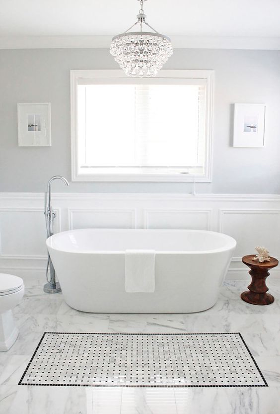 A Peaceful Bathroom In Neutral Shades With Large Crystal Chandelier And Free Standing
